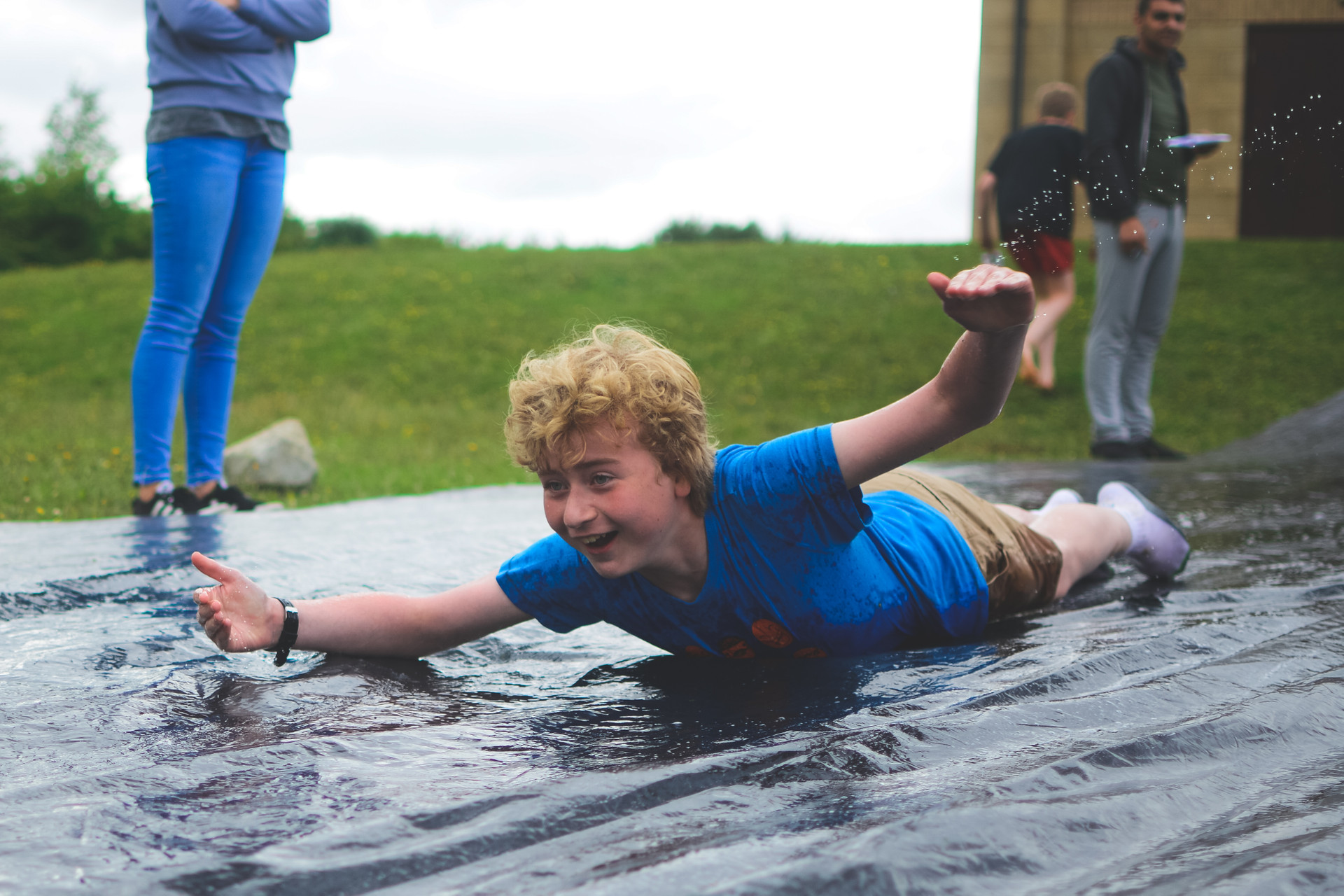 A camper enjoying the water games, sliding down a hill.