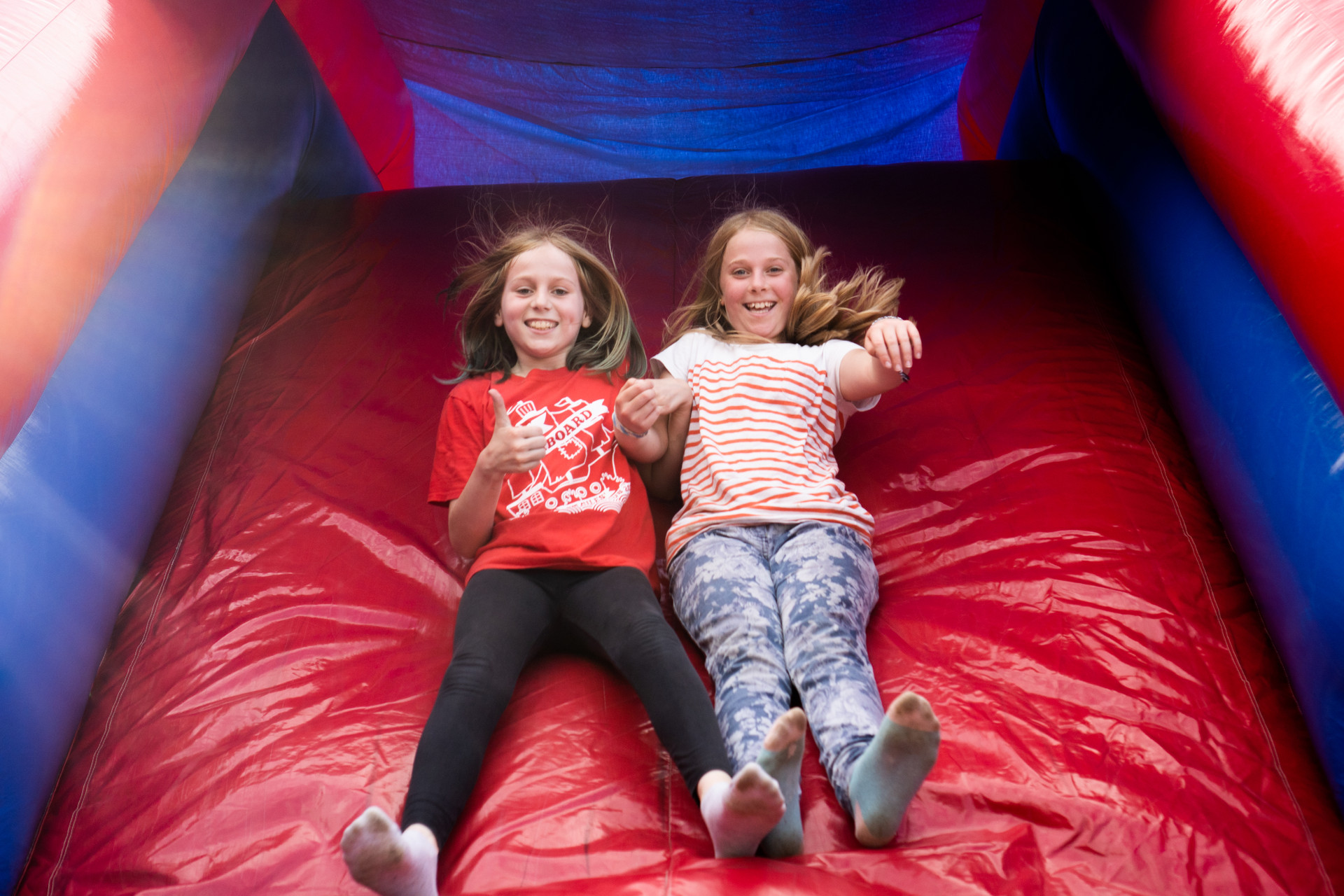 Two smiling campers on an inflatable obstacle course